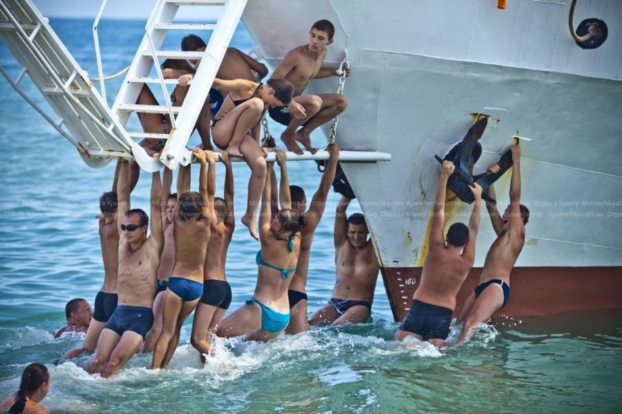 Люди, держащиеся за корабль в Рыбачьем